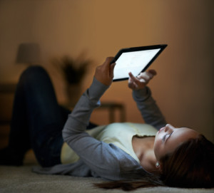 Woman reading digital tablet at night