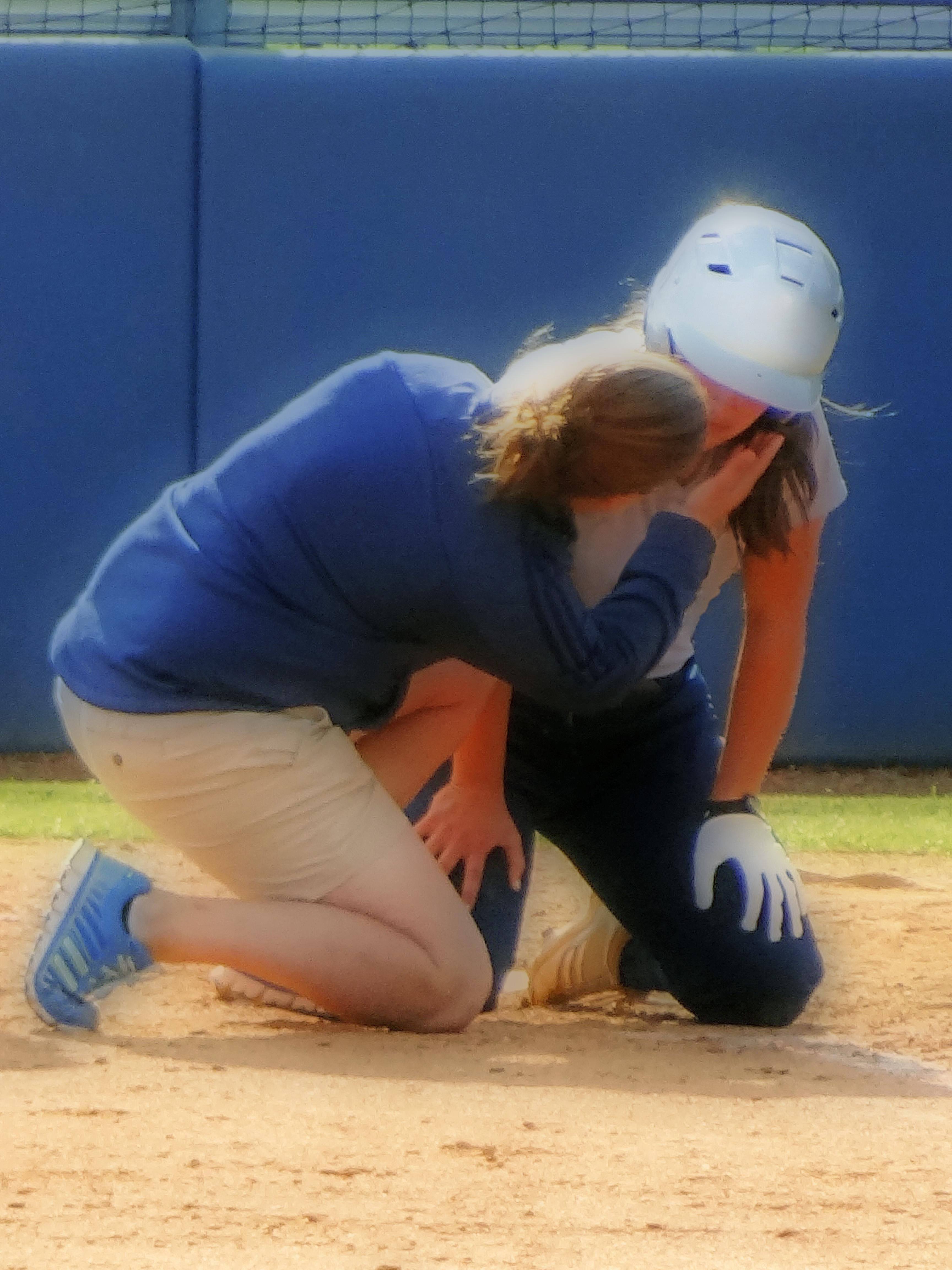 softball player kneeling with injury