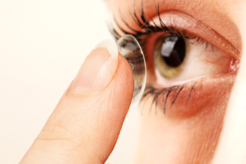 Woman inserting contact into eye